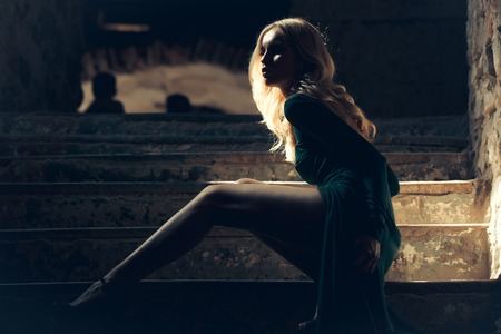 屋内の暗い背景に階段の上に座って裸のバック美しい脚、官能的な緑のゴージャスなドレスを着たブロンドの髪を持つ若い女性
