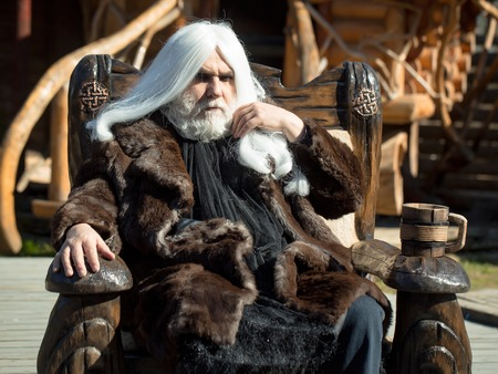 druid: Druid old man with long silver hair beard in fur coat sits in chair with wooden mug on blurred background Stock Photo