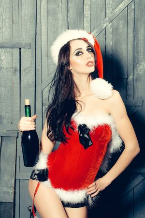 corked: Attractive woman in Santa Claus corset and red hat in studio on wooden background with corked wine bottle Stock Photo