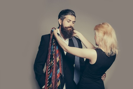 hair tie: young fashionable couple of woman with pretty face and blonde hair and handsome bearded man with long beard in black jacket and tie in studio on grey background Stock Photo