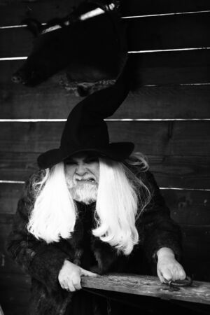 silver hair: Brutal druid old man with long silver hair and beard in Halloween hat opens vintage wooden chest black and white on log house background Stock Photo