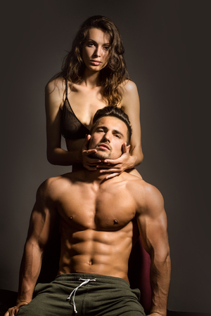 young sexy couple of pretty woman in black bra with wet hair and handsome macho man with muscular torso and athletic body in studio on grey background
