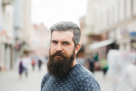 hairy closeup: handsome sexy bearded young man hipster with long beard and mustache has stylish hair on serious hairy face outdoor, closeup Stock Photo