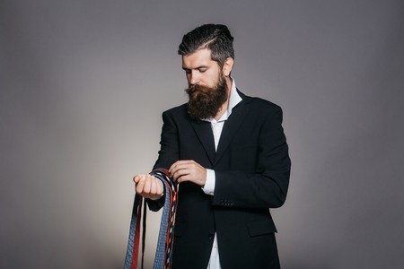 splendid: Handsome man with serious face and splendid beard in elegant jacket hanging many colorful ties on his hand posing on gray background studio