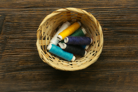 basket embroidery: Many bobbins of bright colorful cotton threads for sewing laying in straw basket on wooden background