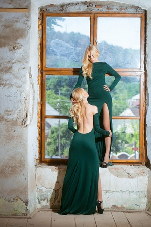 sisters sexy: young pretty women with long lush curly blonde hair and thoughtful face in green dress standing near stony wall and big window sunny day