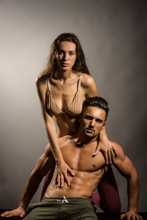muscular body: young sexy couple of pretty woman in beige bra with wet hair and handsome macho man with muscular torso and athletic body in studio on grey background Stock Photo