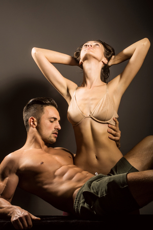 macho: young sexy couple of pretty woman in beige bra with wet hair and handsome macho man with muscular torso and athletic body in studio on grey background Stock Photo
