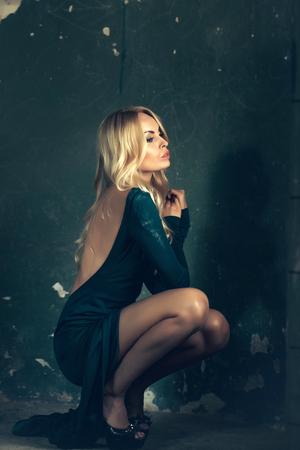 어두운 배경에 벌집에 벌거 벗은 다시 앉아 녹색 드레스 입은 매력적인 얼굴로 관능적 인 여자
