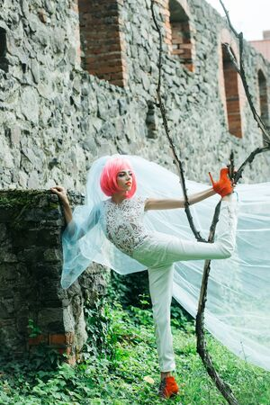ancient sexy: Young girl bride with pretty face glamour makeup with bright pink hair in white sexy wedding suit bridal veil and orange shoes posing near tree with her leg up on stone wall background