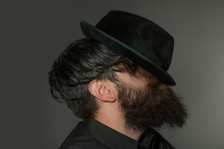 black head and moustache: handsome bearded young man hipster or gentleman with long beard and mustache in stylish black retro hat on serious face in studio on grey background, portrait