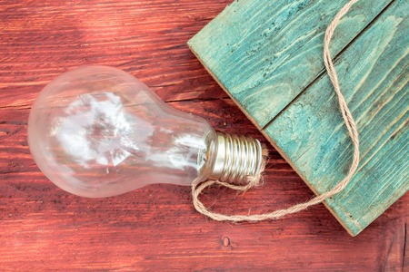 electric bulb: Incandescent light bulb electric glass with rope on wooden background