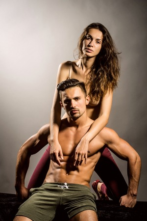 young sexy couple of pretty woman in beige bra with wet hair and handsome macho man with muscular torso and athletic body in studio on grey background Stock Photo