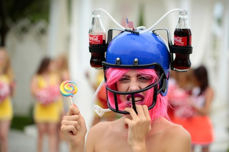 sexy lollipop: Ukraine, Kyiv - July 28, 2016: young patriotic sexy woman with pretty smiling face and pink hair in american football drink helmet with coca cola and lollipop celebrating independence day usa Editorial