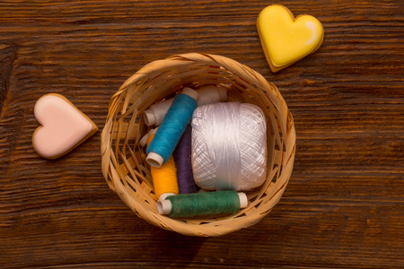 basket embroidery: Many bobbins of bright colorful cotton threads for sewing laying in straw basket with homemade cookies in heart shape on wooden background