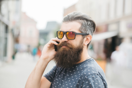 hairy closeup: handsome sexy bearded young man hipster with long beard and mustache has stylish hair on serious hairy face in sun glasses speaking on mobile phone outdoor, closeup Stock Photo
