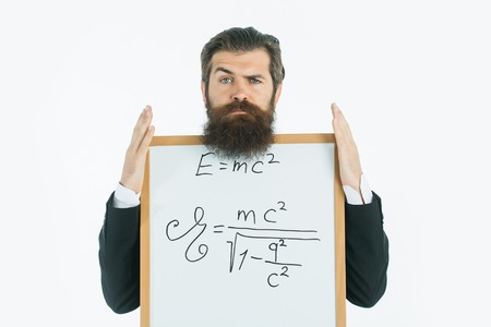 young handsome bearded man scientist or professor with long beard holding teacher board with einstein formula and newtons law isolated on white background Imagens - 60441648