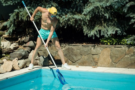 young handsome macho man cleaner with athletic muscular fit sexy body working at swimming pool deck cleaning blue water sunny day outdoor at summer Stock Photo