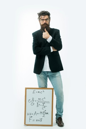 young handsome bearded man scientist or professor in glasses with long beard holding teacher board with einstein formula and newtons law isolated on white background Stock Photo