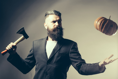 ax man: Handsome young man with long beard and moustache in black jacket holding halloween pumpkin and axe in studio on grey background Stock Photo