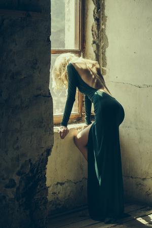 Jonge vrouw met blond haar, gekleed in groene sexi jurk met blote rug die zich voordeed in de buurt van oude venster indoor Stockfoto