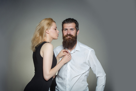 long beard: young couple of woman with pretty face and blonde hair in black vest and handsome bearded man with long beard in white shirt in studio on grey background Stock Photo