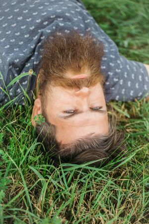 handsome sexy bearded young man hipster with long beard and mustache on thoughtful face relax and laying on green grass field outdoor on natural background