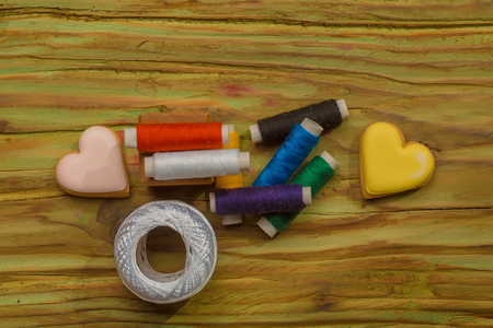 Many bobbins of bright colorful cotton threads for sewing homemade cookies in heart shape and hank of yarn on wooden background 写真素材