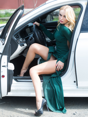 open legs: Young woman blonde with pretty face and long sexy legs dressed in beautiful green dress posing in white car with open door outdoor