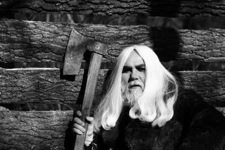 druid: Old man druid with long silver hair and beard in fur coat holding big sharp axe on wooden house background sunny day outdoor, black and white