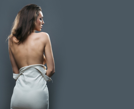 bare girl: young pretty woman with slim sexy body standing with bare back in white dress in studio on grey background, copy space