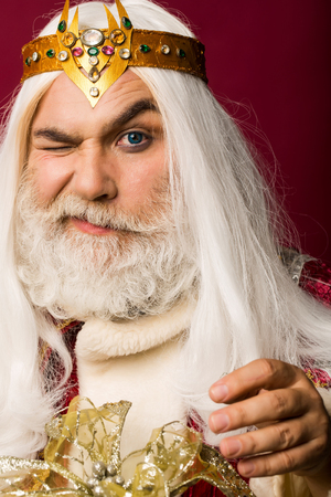 old bearded zeus man wizard in jewellery golden crown with blue lenses in eyes with long gray beard and white hair has winking face on purple background Stock Photo