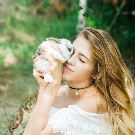 lapin sexy: Jolie jeune femme aux cheveux longs détient mignon petit lapin, le jour d'été sur fond naturel Banque d'images