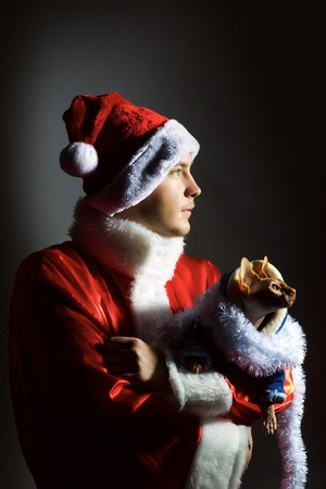 new year cat: young man in red and white santa claus coat and hat at christmas or new year winter holiday holding sphinx cat on hands