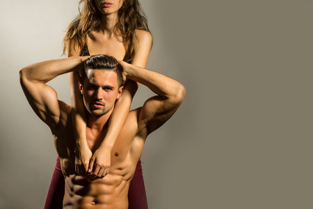 muscle guy: young sexy couple of pretty woman in black bra with wet hair and handsome macho man with muscular torso and athletic body in studio on grey background, copy space