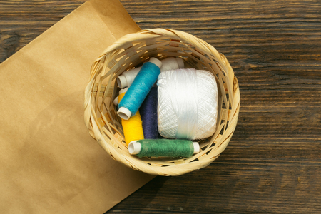 basket embroidery: Many bobbins of bright colorful cotton threads for sewing laying in straw basket with paper on wooden background