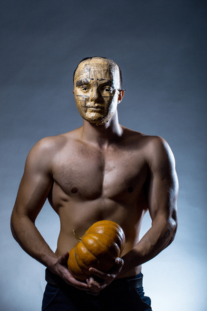bare chest: Young handsome man in mask of newspaper with muscular body bare chest and torso posing in studio holding yellow halloween pumpkin on grey background