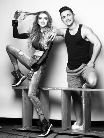 Young couple sitting in studio. Beauty and fashion, friends, black and white