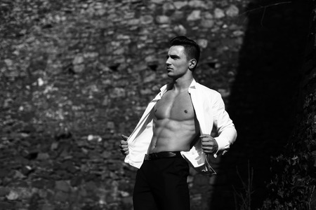 barechested: Man half face bare-chested young handsome sensual model in shirt gaped open poses outside black and white on masonry background Stock Photo