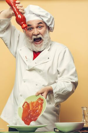 catsup: Bearded chef with ketchup bottle and emotional face in white uniform and hat on yellow background