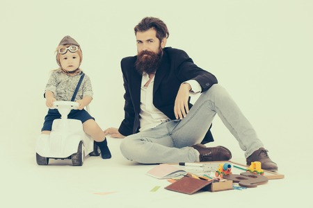 small boy kid driver or pilot sitting on plastic toy cat in stylish shirt with bearded man father with beard near school appliances of blackboard letter pen and paper isolated on white background