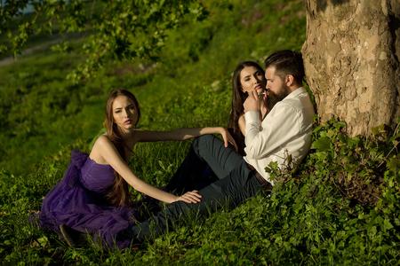 joven fumando: hombre guapo con barba en camisa blanca fumar cigarrillos de estar con dos mujeres muy jóvenes en vestidos de violeta cerca del árbol en la hierba verde el día soleado al aire libre