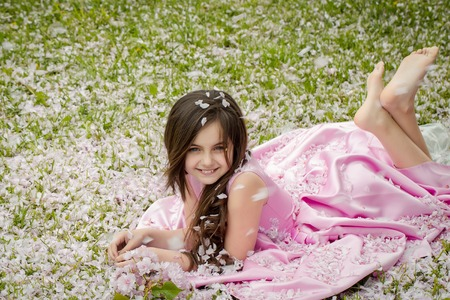 little girl barefoot: Beautiful little girl in pink dress with long brunette hair and smiling happy face lying barefoot on green grass covered with spring flower blossom petals outdoor