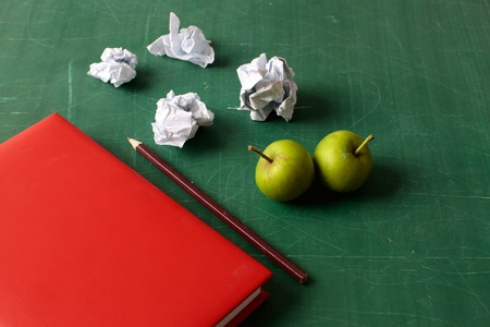 screwed: Red notebook screwed pieces of paper colored pencil and green apples laying on school blackboard background