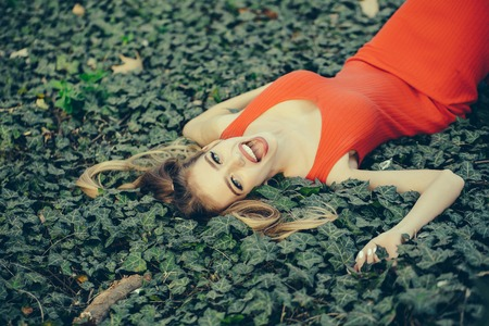 feminity: Beautiful young woman with red lips in fashion dress lying in the green grape vine leaves