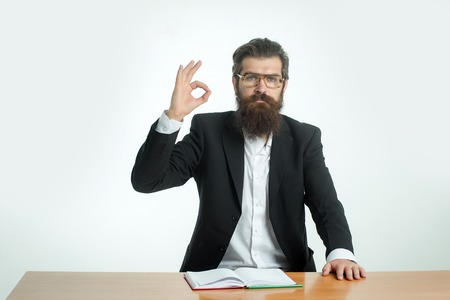 okey: young handsome bearded man scientist or professor with long beard and teacher glasses with book or notepaper sitting at table with okey gesture isolated on white background