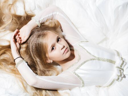prom dress: small girl kid with long blonde hair and pretty serious face in prom dress lying on white fabric, closeup