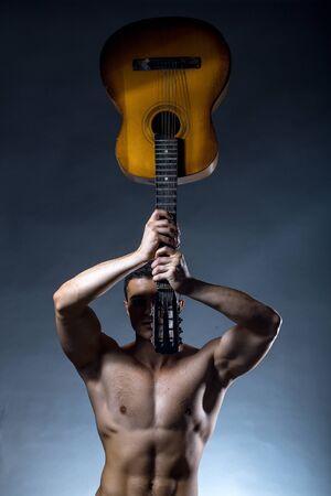 nackte brust: Junger stattlicher Mann mit muskul�sen K�rper nackte Brust und Oberk�rper posiert im Studio akustische Gitarre auf grauem Hintergrund