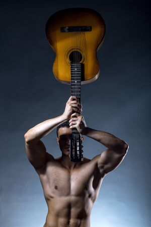 bare chest: Young handsome man with muscular body bare chest and torso posing in studio holding acoustic guitar on grey background Stock Photo