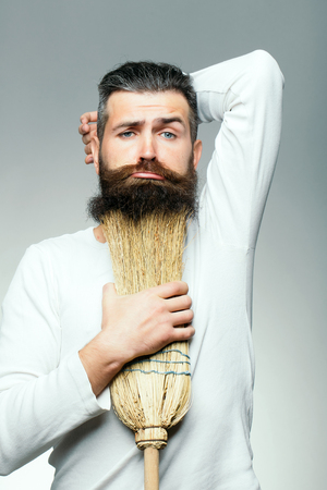 grimace: Bearded man with grimace face in white shirt holding broom as beard in studio on grey background